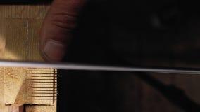Il carpentiere dell'artigiano fa un taglio su un pettine di legno con un primo piano della sega della mano 4 K archivi video