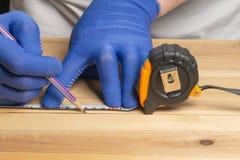 Il carpentiere in guanti blu con una matita segna lo spazio in bianco per mobilia fatta di legno immagine stock