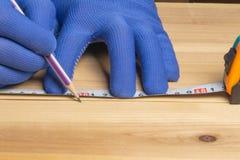 Il carpentiere in guanti blu con una matita segna lo spazio in bianco per mobilia fatta di legno fotografia stock