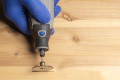 Il carpentiere in guanti protettivi blu tratta il dremel di legno fotografia stock