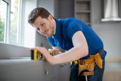 Il carpentiere Installing Luxury Modern misura la cucina immagine stock