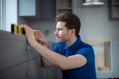 Il carpentiere Installing Luxury Modern misura la cucina fotografia stock libera da diritti