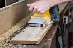 Il carpentiere lavora con la smerigliatrice a nastro in carpenteria Immagini Stock
