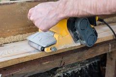 Il carpentiere lavora con la smerigliatrice a nastro in carpenteria Immagine Stock