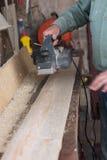 Il carpentiere lavora con la smerigliatrice a nastro in carpenteria Immagine Stock Libera da Diritti