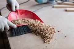 Il carpentiere nell'officina di carpenteria sta spazzando la segatura, Immagine Stock
