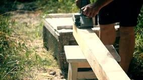 Il carpentiere spiana un fascio con la piallatrice di legno elettrica video d archivio
