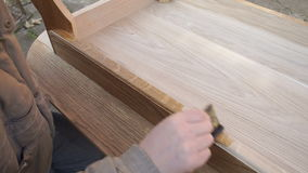 Il carpentiere sta coprendo la tavola dalla lacca stock footage