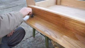 Il carpentiere sta coprendo la tavola dalla lacca video d archivio