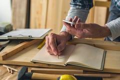 Il carpentiere sta scrivendo le note del progetto mentre per mezzo dello smartphone fotografia stock