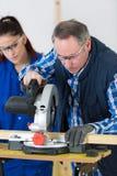 Il carpentiere Teaching Apprentice How per usare la circolare ha visto Fotografie Stock Libere da Diritti