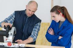 Il carpentiere Teaching Apprentice How per usare la circolare ha visto Immagini Stock Libere da Diritti