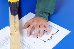 Il carpentiere tiene la macchina dell'perforare-alesaggio immagini stock libere da diritti