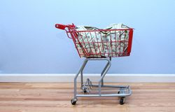 Il carrello di acquisto rosso ha riempito di soldi Fotografie Stock