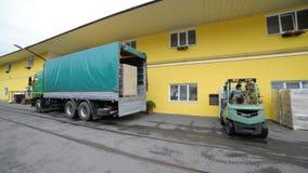 Il carrello elevatore carica i pallet con le scatole nel camion video d archivio