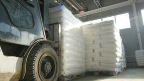 Il carrello elevatore di vista laterale del primo piano prende e trasporta il mucchio della borsa archivi video