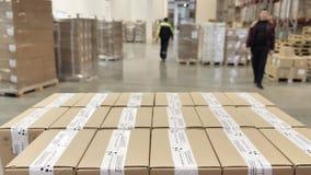 Il carrello elevatore a forcale con le scatole di cartone si muove ad un magazzino moderno archivi video