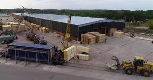 Il carrello elevatore porta un fascio di legno, trasporto di carico nella fabbrica Processo del lavoro in uno stabilimento per la video d archivio