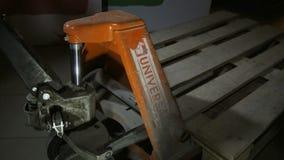 Il carrello elevatore potente sporco arancio del primo piano tiene i pallet di legno video d archivio