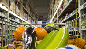 Il carrello ha riempito con i prodotti alimentari fra gli scaffali di un supermercato Vista dal punto di vista del cliente Fotografia Stock Libera da Diritti