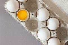 Il cartone del pollo crudo eggs su fondo grigio Uovo rotto tuorlo Immagine Stock