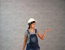 Il casco bianco degli articoli della donna del tecnico con il grembiule grigio dei jeans del denim e della maglietta veste la con fotografia stock