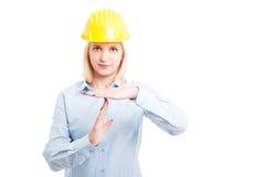 Il casco d'uso dell'architetto femminile che mostra il tempo fuori gesture immagini stock libere da diritti