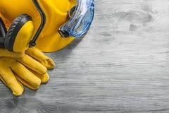 Il casco dei guanti dei vetri di protezione della cuffia sul bordo di legno cons Fotografia Stock