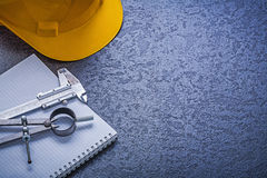 Il casco della costruzione del taccuino fa il giro della costruzione co della scala a nonio Fotografia Stock Libera da Diritti