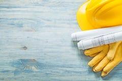 Il casco ha rotolato i guanti protettivi dei disegni di costruzione su woode Fotografia Stock Libera da Diritti