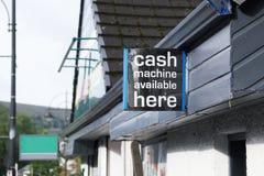 Il cash machine qui libera i ritiri lavora il segno a macchina sulla parete fotografie stock