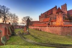 Il castello dell'ordine teutonico in Malbork al tramonto Immagine Stock