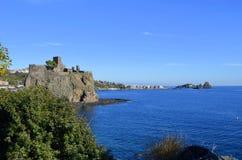 Il castello di Acicastello e le pile di Acitrezza. immagine stock