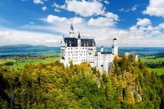 Il castello famoso del Neuschwanstein, palazzo di fiaba su una collina irregolare sopra il villaggio di Hohenschwangau vicino al  Immagine Stock