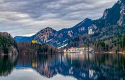 Il castello il Neuschwanstein e Hohenschwangau è riflesso nel Alpsee, Baviera, Germania - gennaio 19,2018 Immagine Stock Libera da Diritti