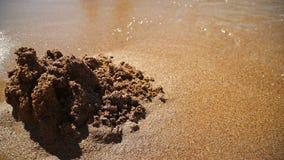 Il castello sulla sabbia è rimosso da un'onda del mare stock footage