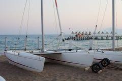 Il catamarano sta sulla spiaggia sabbiosa del mare Immagini Stock