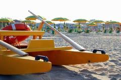 Il catamarano sulla priorità alta sulla spiaggia vuota con molti lettini ed ombrelli sui precedenti Fotografie Stock Libere da Diritti