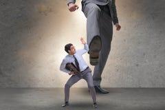 Il cattivo capo arrabbiato che dà dei calci all'impiegato nel concetto di affari Fotografia Stock Libera da Diritti