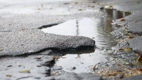 Il cattivo pozzo dell'asfalto è grande strada all'aperto della pioggia della pozza video d archivio