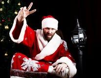 Il cattivo rastoman Santa Claus che fa il dito differente firma sui precedenti dell'albero di Natale Fotografie Stock