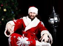 Il cattivo rastoman Santa Claus che fa il dito differente firma sui precedenti dell'albero di Natale Fotografia Stock Libera da Diritti