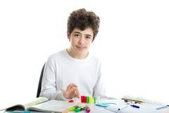 Il Caucasian liscio-ha pelato il ragazzo che gioca con i domino su compito Immagine Stock