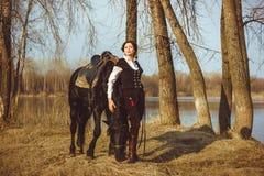 Il cavaliere accanto al cavallo Immagine Stock