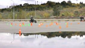 Il cavaliere che fila sul motociclo fra i coni di traffico video d archivio