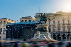 Il cavaliere con una scultura del leone sta sedendo su molti piccioni nella piazza del Duomo a Milano, Italia immagini stock