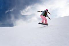 Il cavaliere della ragazza salta sullo snowboard Fotografie Stock
