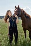 Il cavaliere della ragazza sta accanto al cavallo nel campo Il ritratto di modo di una donna e le giumente sono cavalli nel villa immagine stock libera da diritti