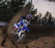 Il cavaliere di motocross crea una nuvola di polvere e di detriti Fotografie Stock Libere da Diritti
