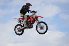 Il cavaliere di motocross salta, cielo blu Fotografie Stock Libere da Diritti
